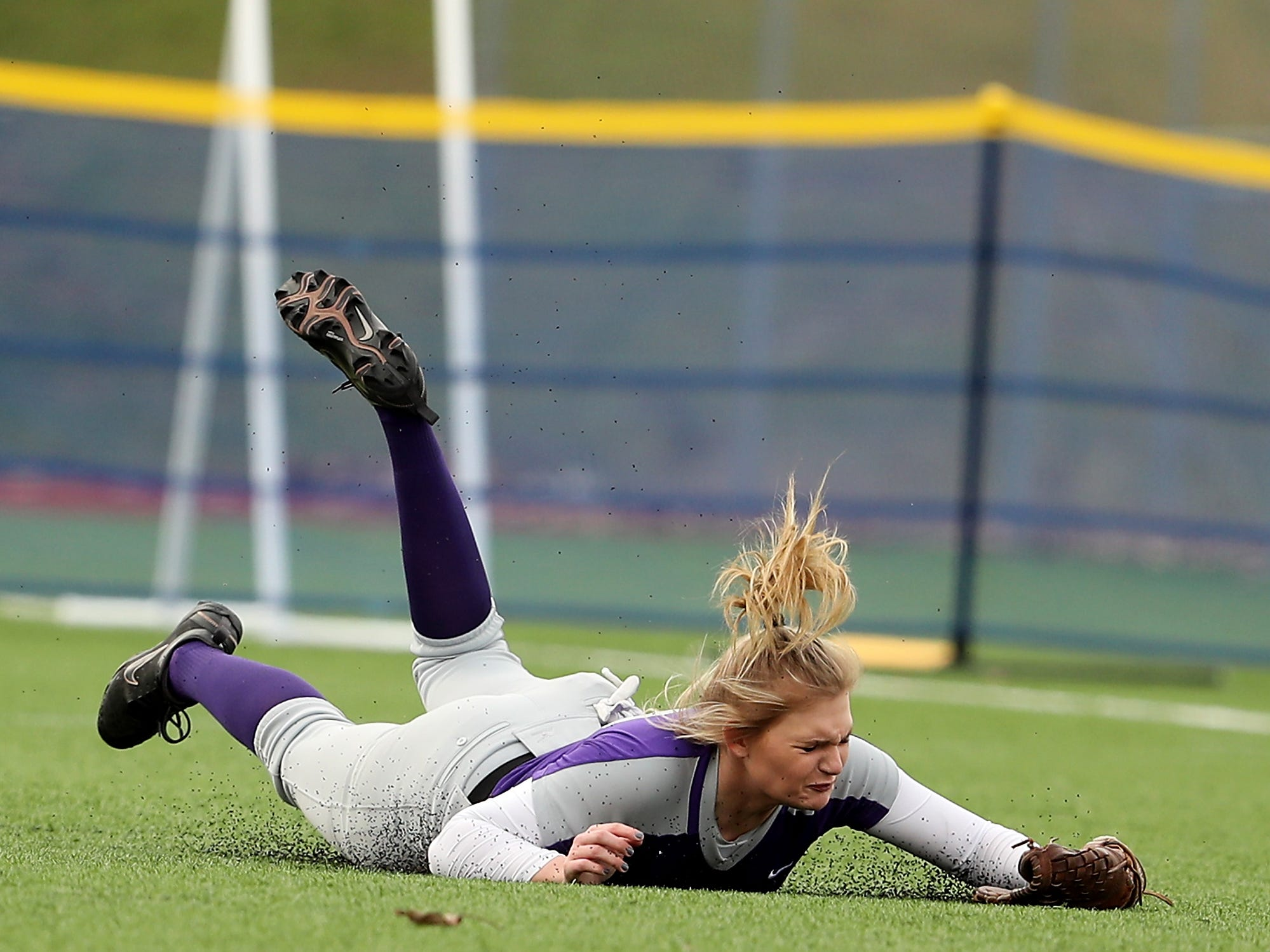 North Kitsap's Makayla Stockman makes a dive and hits the turf while trying for a fly ball during their game against Olympic at Gene Lobe Field on Wednesday, March 27, 2019.