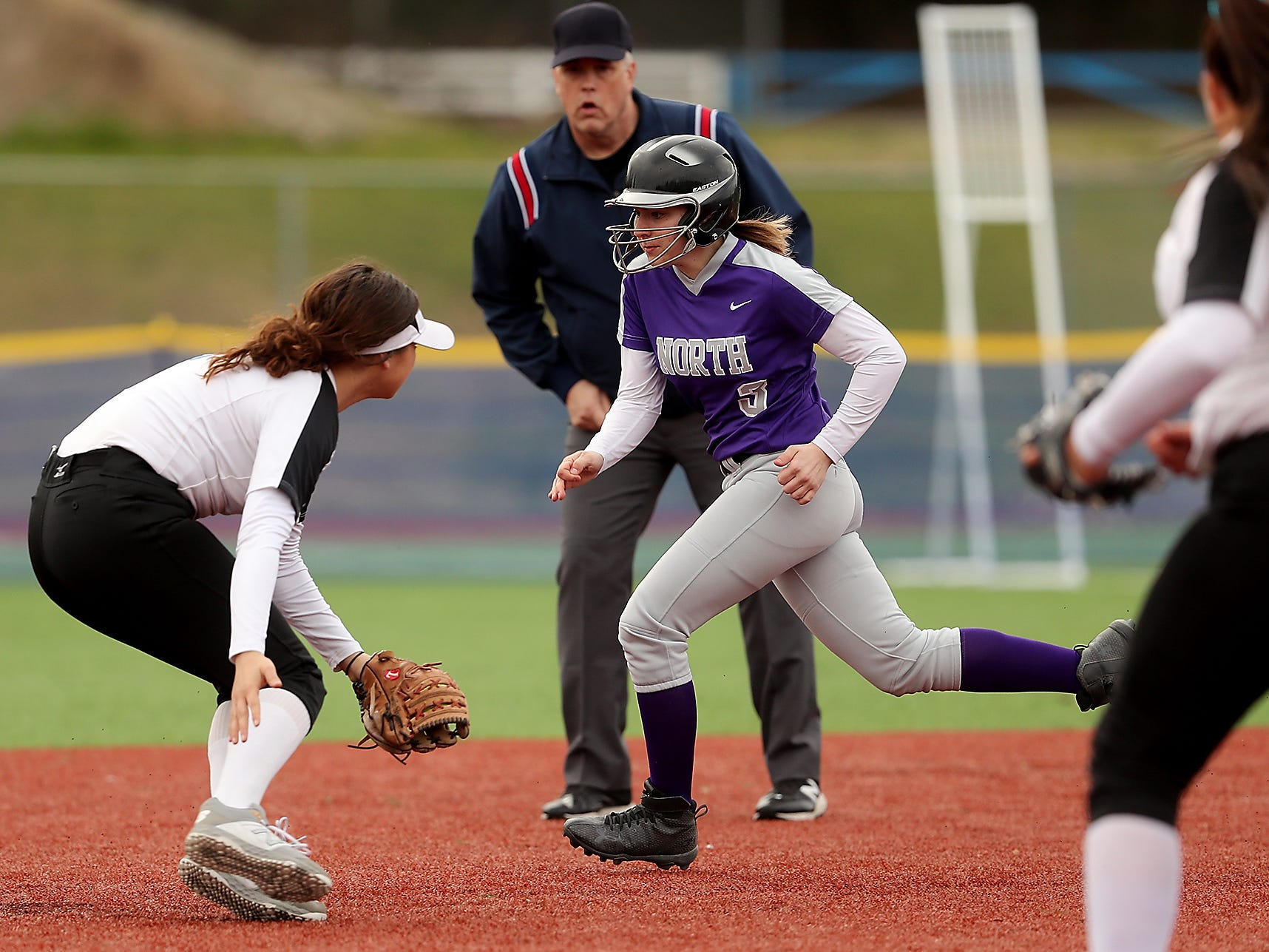 North Kitsap's Olivia Holmbery (3) tries to make a run around Olympic's Vanisa Ivie (left) who has the ball in glove at Gene Lobe Field on Wednesday, March 27, 2019. Holmbery was tagged out by Ivie.