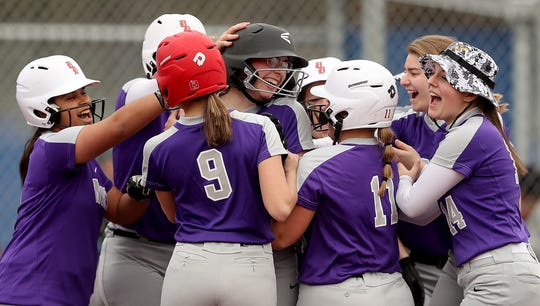 North Kitsap's Samantha Burgh (center) is congratulated by her team at home plate after she hit a grand slam against Olympic at Gene Lobe Field on Wednesday, March 27, 2019.