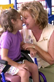 Betsy Farmer, then executive director of Space Coast Early Intervention, is shown in this 1999 photo with student Madison Van Buskirk.