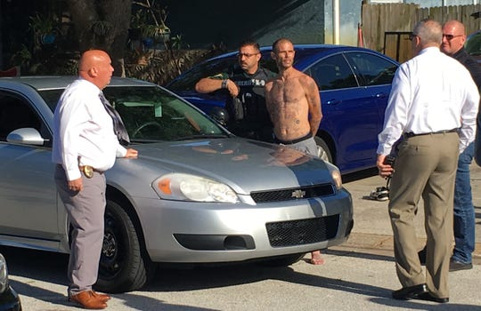 Police lead handcuffed man to detectives