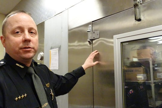Crawford County Sheriff Scott Kent points out a hinge on a refrigeration unit in the jail's kitchen that is due to be replaced soon.