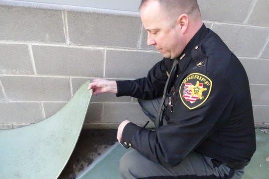 Crawford County Sheriff Scott Kent shows a spot where the ground cover in the jail's yard has become loose.