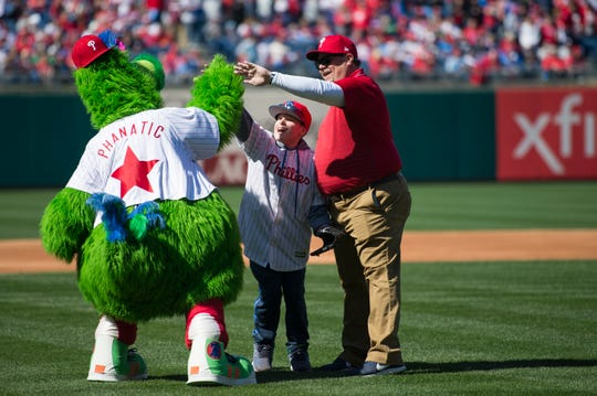 Daniel Scharff, a fourth-grader at St. Rose of Lima School in Haddon Heights with cerebral palsy, celebrates with the Phillie Phanatic after Scharff threw out the ceremonial Opening Day first pitch at the Phillies-Braves game at Citizens Bank Park in Philadelphia on Thursday, March 28, 2019.