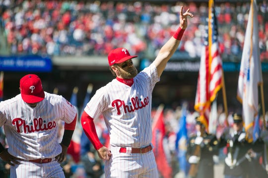 Bryce Harper gestures towards the crowd as he is introduced prior to the Phillies Opening Day game between the Phillies and the Braves at Citizens Bank Park in Philadelphia on Thursday, March 28, 2019.