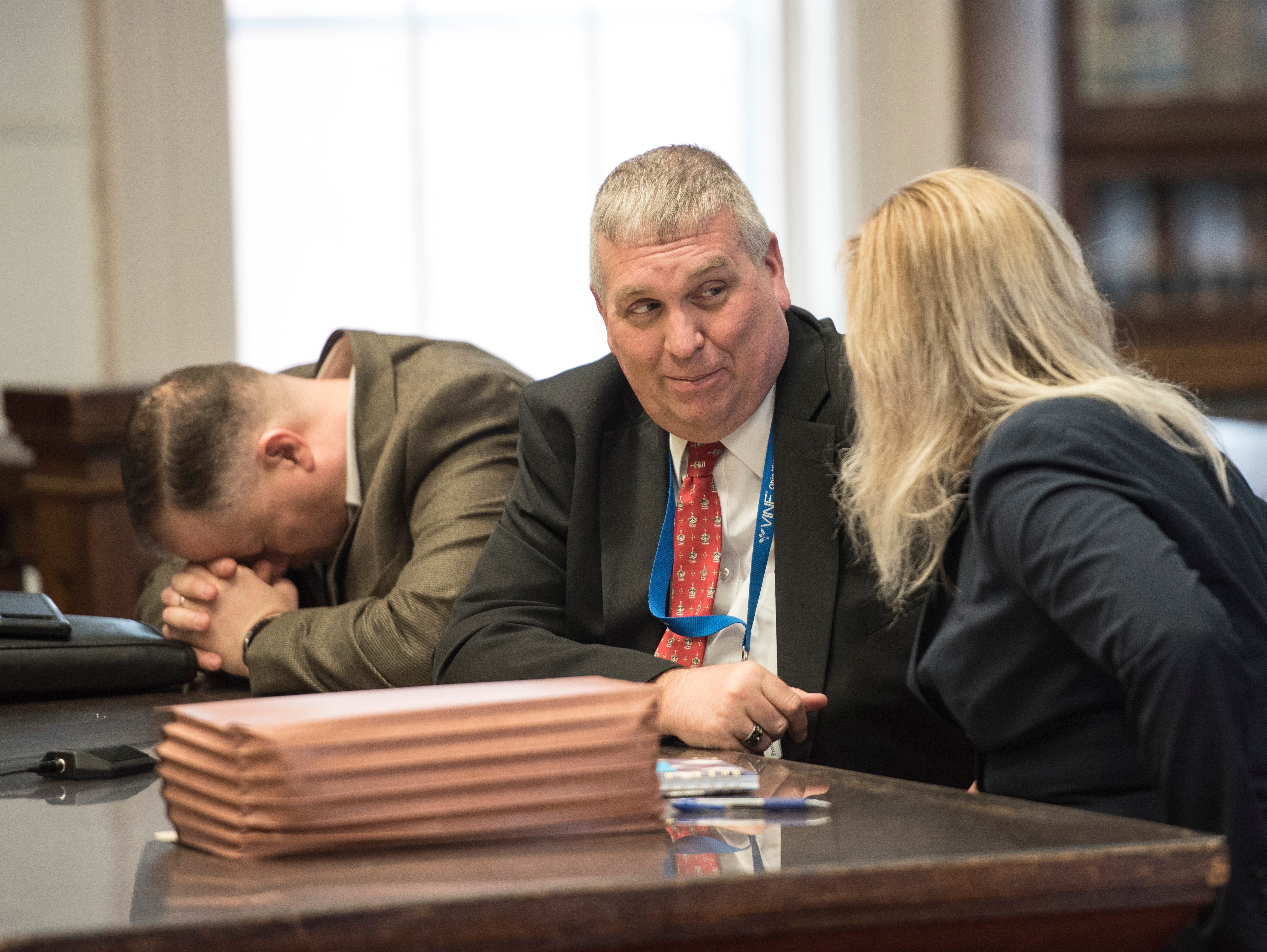A BCI agent, left, lays his head down as Special Prosecutor Angie Canepa talks with Pike County Prosecutor Rob Junk before Rita Newcomb's pretrial hearing on March 28, 2019. Newcomb, 65, of South Webster, is accused of perjury and obstructing justice for allegedly misleading investigators concerning the deaths of the eight members of the Rhoden family in 2016 and is also charged with forging custody documents to cover up the crimes.