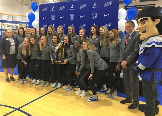 Thomas More players pose with their new national championship trophy as Thomas More University, on March 27, 2019,  unveiled the banner for the 2019 Division III national championship in women's basketball that the Saints won earlier in the month.