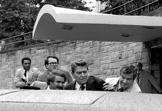 President Ronald Reagan is shoved into the president's limousine by secret service agents after being shot outside the Washington Hilton hotel on March 30, 1981.