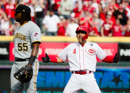 Cincinnati Reds shortstop Jose Iglesias celebrates after hitting an RBI double to score Reds second baseman Jose Peraza during the second inning of their Opening Day game against the Pittsburgh Pirates on Thursday, March 28, 2019, at Great American Ball Park in Cincinnati.