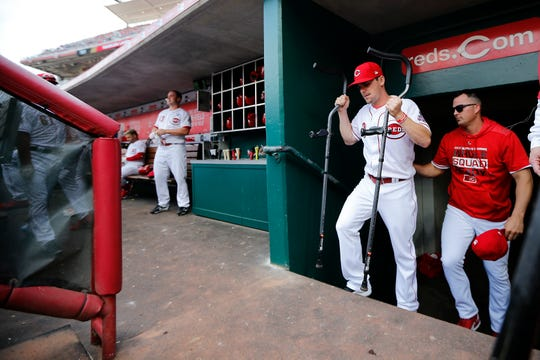 Injured Cincinnati Reds second baseman Scooter Gennett (3) walks in the dugout with crutches in the third inning of the Opening Day game between the Cincinnati Reds and the Pittsburgh Pirates at Great American Ball Park in downtown Cincinnati on Thursday, March 28, 2019.