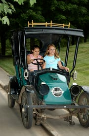 In this photo provided by Kings Island, two children ride in an antique car, part of a returning attraction at the park.