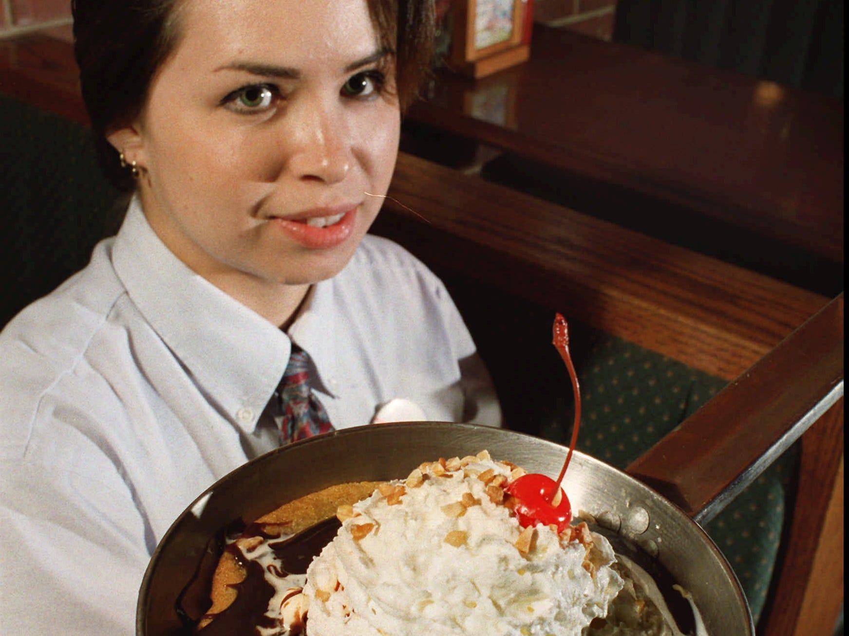 "From 1995: Cheddar's server worker Nikki Katayama shows off the restaurant's legendary ""Cookie Monster"" dessert."