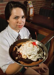 "From 1995: Cheddar's server worker Nikki Katayama shows off the restaurant's legendary ""Cookie Monster"" dessert."