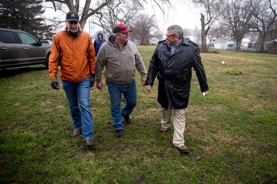 Mike Naig, Iowa's secretary of agriculture, Mike Stenzel, a farmer from Hamburg, and Bill Northey, undersecretary in the U.S. Department of Agriculture, discuss the damage to surrounding farmland during recent flooding on Thursday, Mach 28, 2019, in Hamburg.