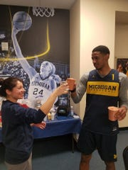 Tiffany Ilten and U-M basketball player Charles Matthews tasting a smoothie he made.