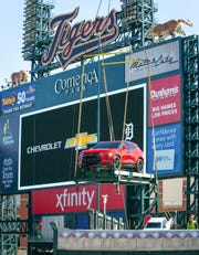 A red Chevrolet Blazer RS 2019 is lowered by a crane on Tuesday, March 26, 2019, on a Centerfield platform in the Chevrolet Fountain in Comerica Park