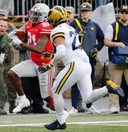 Ohio State receiver Parris Campbell, left, is run out of bounds by Michigan defensive back Tyree Kinnel during the Wolverines' 62-39 loss.