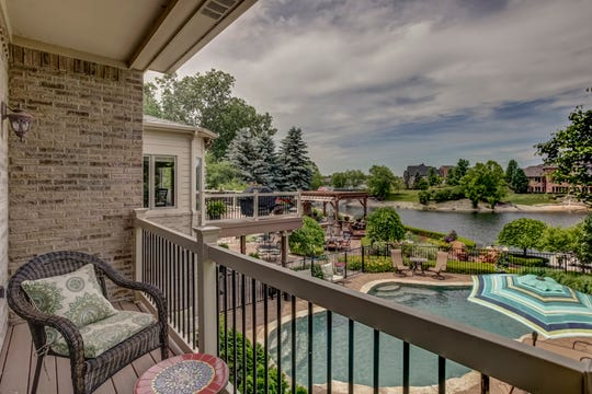 The home features a two-story great room and hearth room that leads to a deck with views of the backyard and nearby lake as well as a pool.