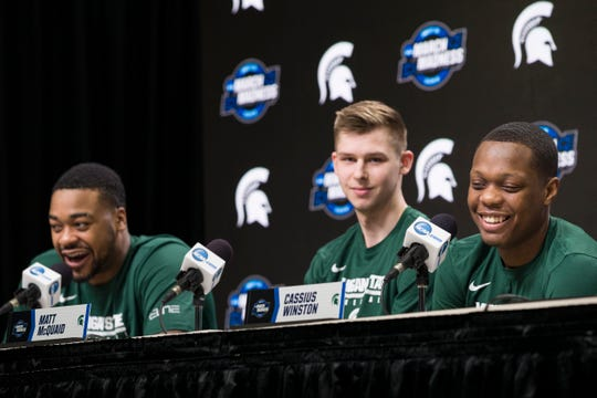 Michigan State's forward Nick Ward, left, guard Matt McQuaid, and guard Cassius Winston smile during a news conference Thursday.