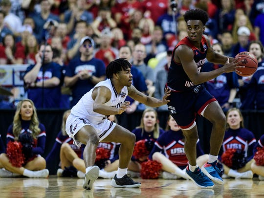 University of Southern Indiana's Kobe Caldwell (0) dribbles around West Texas A&M's Jordan Collins (5) during the NCAA Men's Division II Quarterfinals at Ford Center in Evansville, Ind., Wednesday, March 27, 2019. The Screaming Eagles defeated the Buffs, 94-84, to advance to Thursday's Final Four matchup.