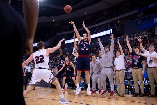 University of Southern Indiana's Nate Hansen (5) shoots a three-pointer over West Texas A&M's Ryan Quaid (22) during their quarterfinal matchup at the NCAA Men's Division II Elite 8 Basketball Tournament at the Ford Center in Evansville Wednesday night.
