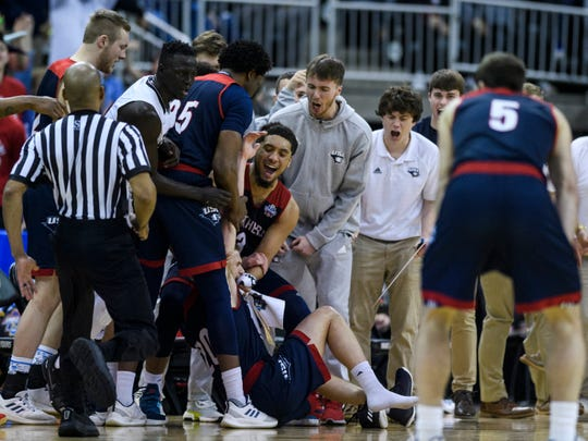 University of Southern Indiana's Alex Stein (20) is caught by his teammates after making a three-pointer, falling backwards and losing his right shoe in the process during the second half against the West Texas A&M Buffs in the NCAA Men's Division II Quarterfinals at Ford Center in Evansville, Ind., Wednesday, March 27, 2019. The Screaming Eagles defeated the Buffs, 94-84, to advance to Thursday's Final Four matchup.