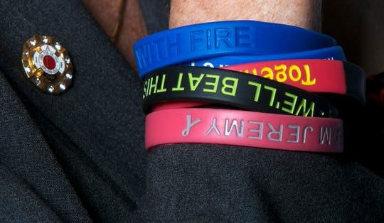 """Heather Mazurkiewicz shows her bracelets supporting firefighters. She is an advocate for getting firefighters cancer coverage. """"When a widow gives you a bracelet, you don't take it off,"""" she said."""