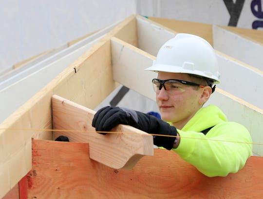 Green Bay Southwest student Gavin Litke works on a roof support beam during construction of a single-family home at 720 N. Broadway by students in the Green Bay School District's Bridges Construction & Renovation program.