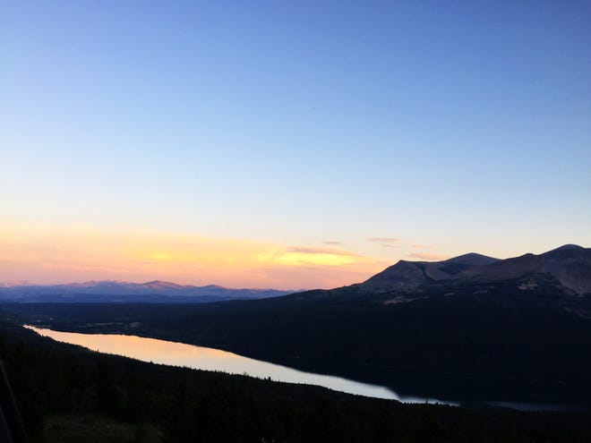 Sunset shines on the water from a viewpoint over the Two Medicine valley of Glacier National Park