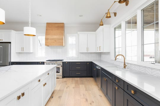 The kitchen features two-toned cabinets, the lower painted navy and upper white, and a large island with room for seating.