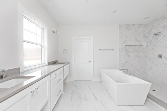 A modern freestanding tub sits in the center of the master bathroom next to a walk-in shower with quartz tiles and two shower heads.