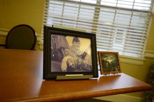 Photos of Buster Sipes sit on a table next to the painting of his airplane that will be a part of an art show at Jackson City Hall in April and will eventually be permanently placed at McKellar-Sipes Regional Airport.