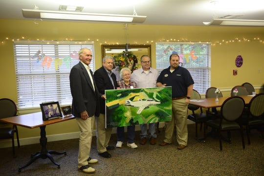 Jackson Mayor Jerry Gist, McKellar-Sipes Regional Airport Director Steve Smith, Phyllis Sipes, Poeration Freedom Warriors Coordinator Franciscus Poppelaars and Brookdale Jackson Oaks Executive Director Clint Hickerson pose for a photo with the painting depicting Buster Sipes' airplane.