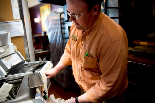 Manager Matt Wegman inserts a bagel into the front load bread slicer at Panera on Cumberland Ave. in Knoxville, Tennessee on Thursday, March 28, 2019.