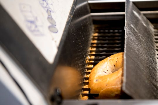A vertically sliced bagel exits the front load bread slicer at Panera on Cumberland Ave. in Knoxville, Tennessee on Thursday, March 28, 2019.