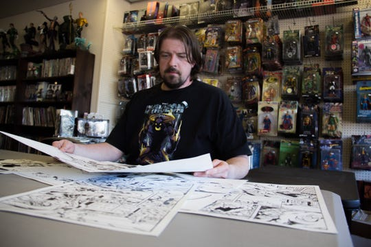 """Author and illustrator Shawn Harbin goes through sketches of characters and scenes from his """"Transfurred"""" comic book March 27 at Comics Exchange in Knoxville. The comic book's hero is detective Jaynie Lain, a 12-year-old transgender girl."""