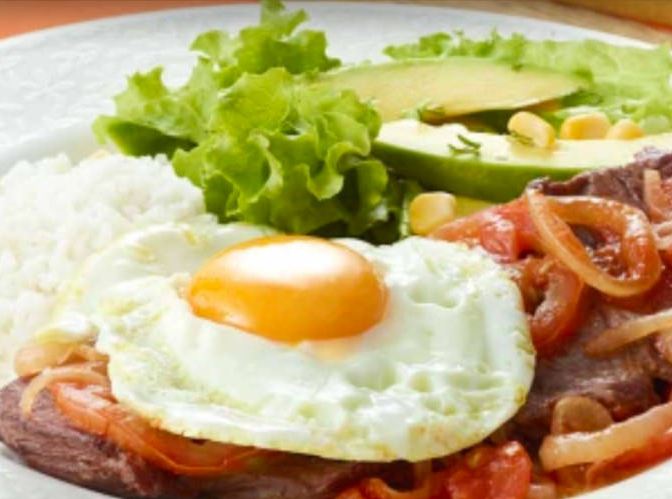 This traditional Colombian dish, bistec a caballo, features a steak smothered in tomatoes and onions and topped with a fried egg.