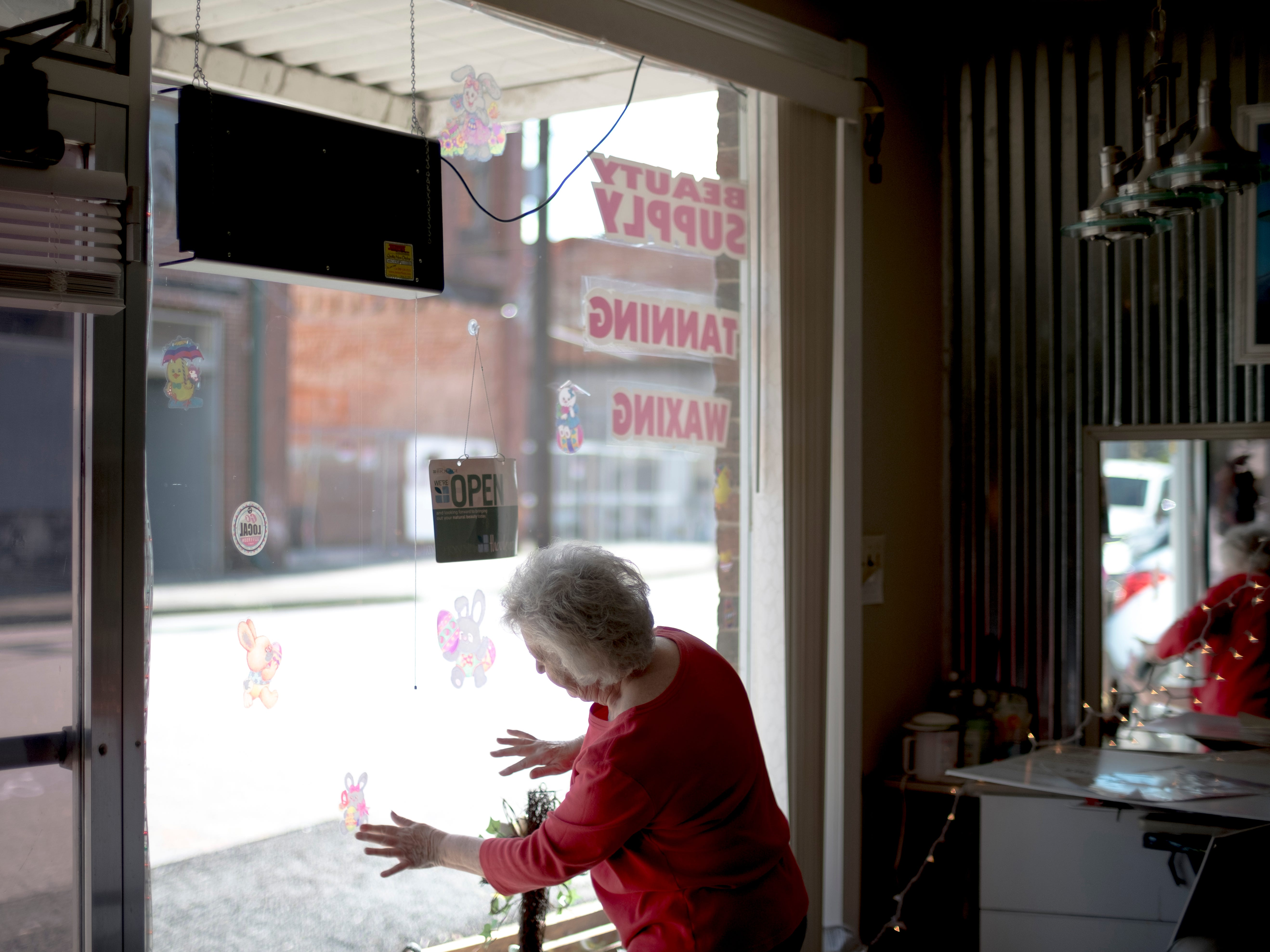 "Hairstylist Ailene Combs, owner of Cloud 9 Hair & Tanning Salon, hangs Easter decorations on the front window of her business on Main Street in Jefferson City, Tennessee on Tuesday, March 26, 2019. On a street where storefronts are boarded up and abandoned, the salon is one of the only businesses remaining. A member of the zoning committee since 2010, Combs has been working to receive funding for the revitalization of downtown. ""It will never be the same it once was,"" Combs says, ""It didn't get into this shape overnight, and it's going to take a lot of people working together."""