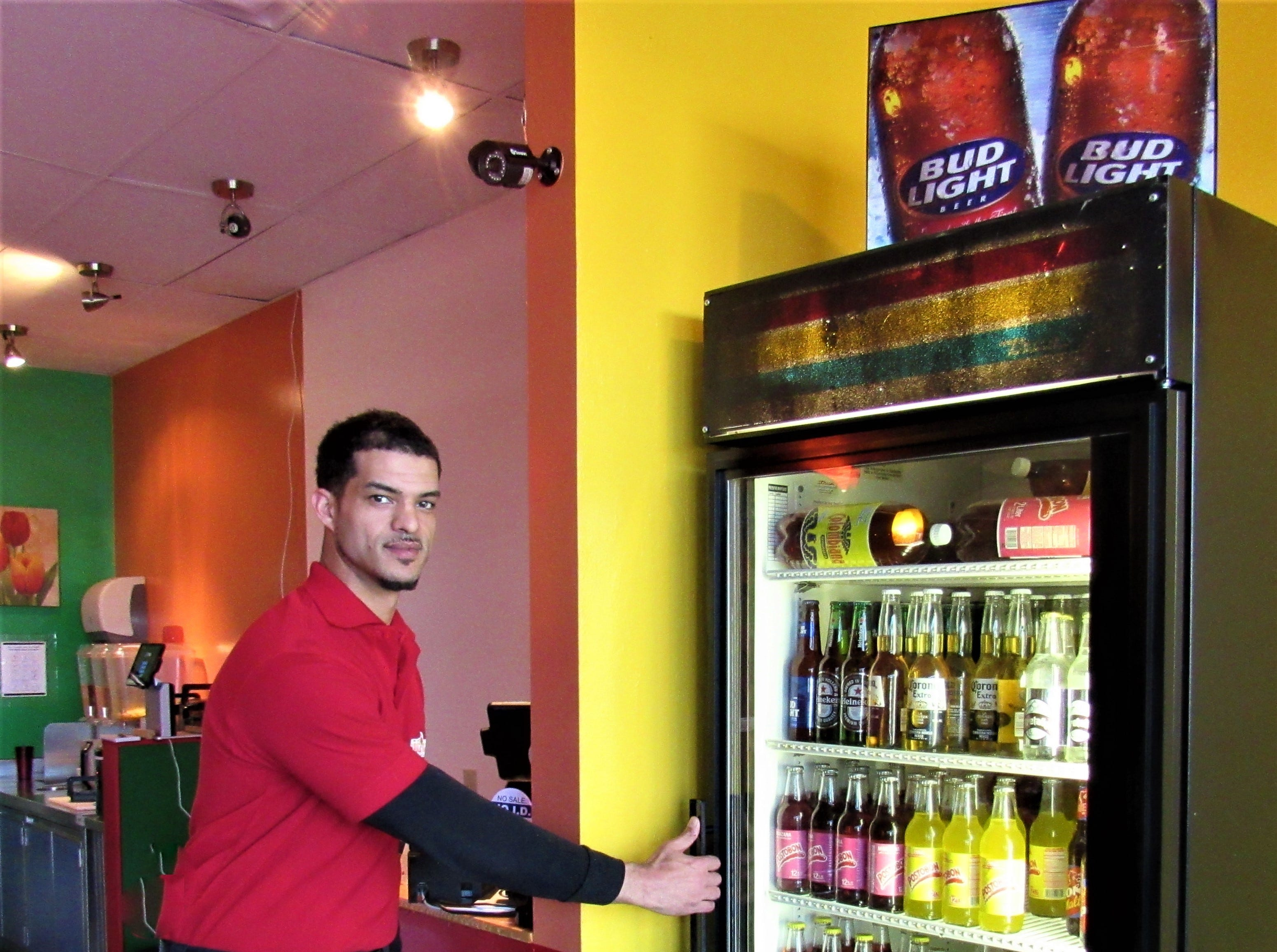 Waiter Jordan Smith reaches into a cooler holding a selection of imported and domestic beer, soft drinks and Postobon, the popular Colombian beverage. March 2019