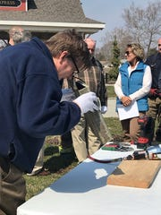 Craig Hadley, executive director for TCHA, examines the contents of the time capsule discovered beneath the Spanish-American War Memorial on Friday. Hadley and his team will examine the papers found inside the box to determine their purpose or message.