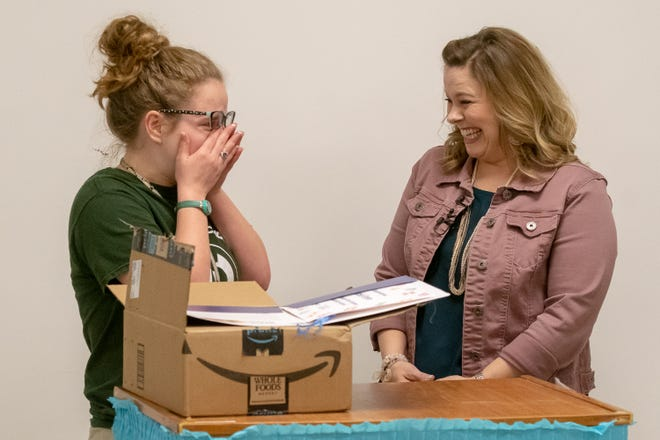 Carencro High senior Ariel Green opens a box from Amazon to find out she will receive a $40,000 college scholarship and a 12-week summer internship with Amazon. Claire Trouard, director of the school's Academy of Information Technology, and fellow faculty are surprising her with the news.
