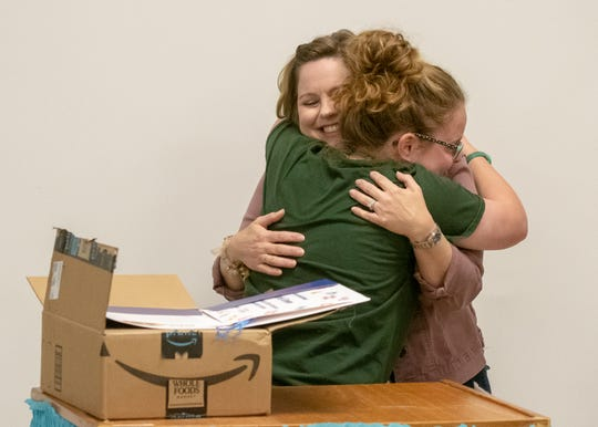 Carencro High senior Ariel Green opens a box from Amazon to find out she will receive a $40,000 college scholarship and a 12-week summer internship with Amazon. She hugs her Claire Trouard, director of the school's Academy of Information Technology, who surprised her with the news.