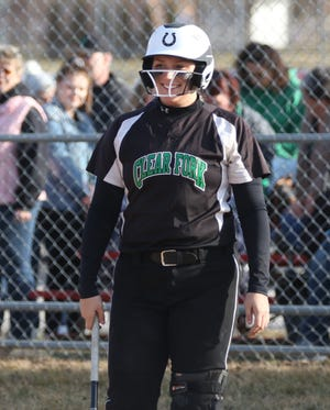 Clear Fork's Haylie Miller shoots a smile to her coach Jeff Gottfried during an at bat at Shelby earlier this season.