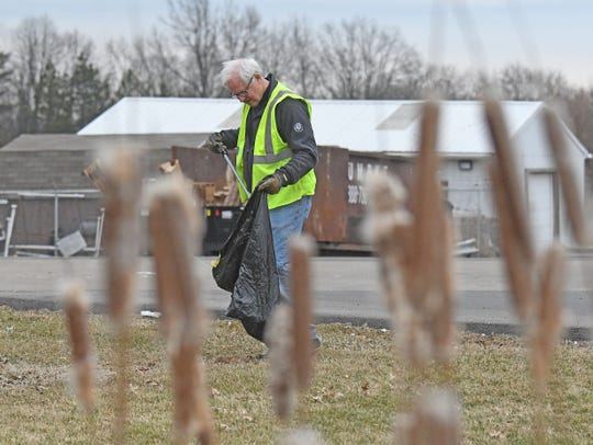 "Doug Versaw picks up litter on March 28 to mark the start of the 23rd annual Earth Stewardship program and the ""Great American Cleanup."""