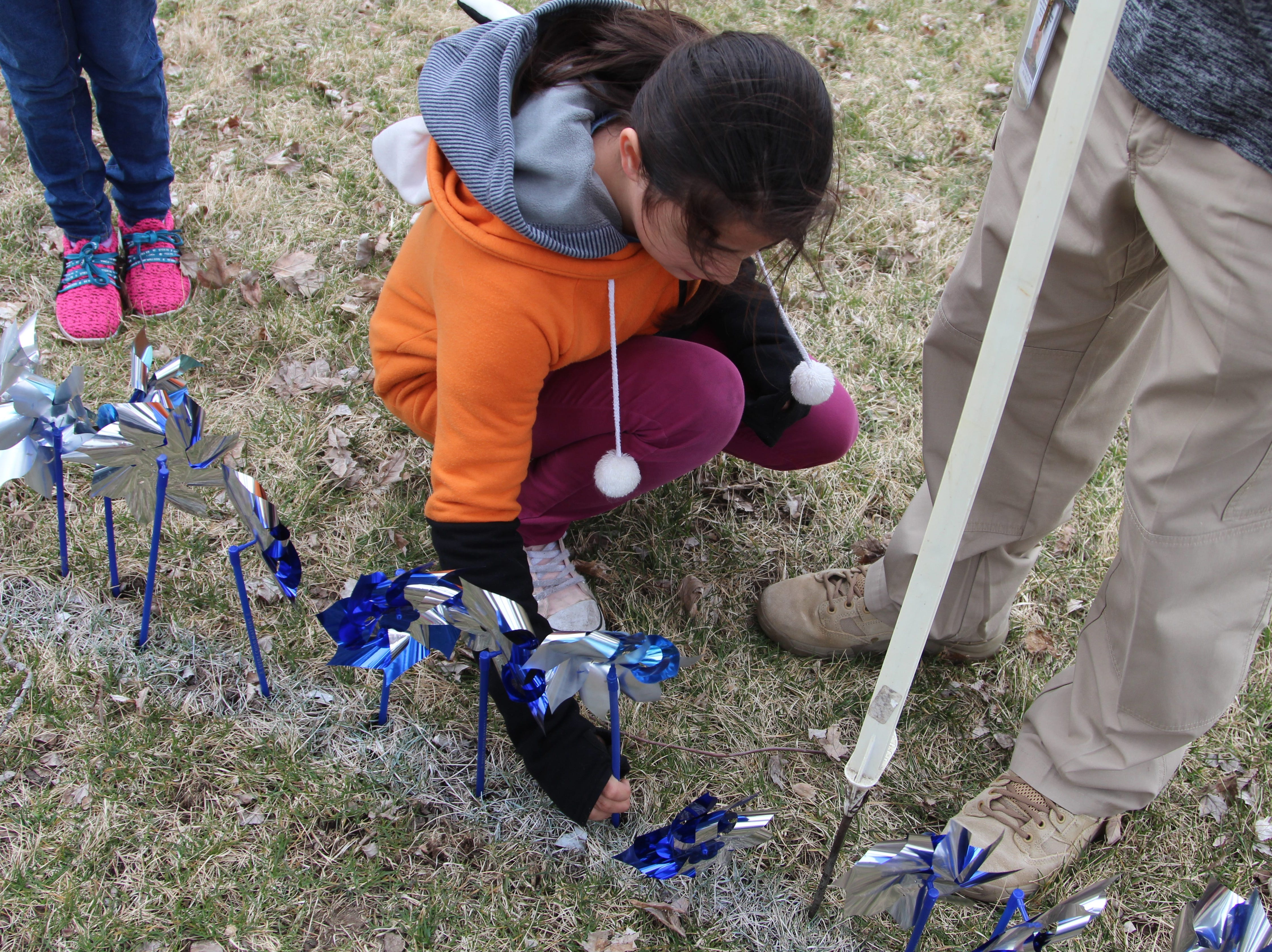 Valerie Riegel with Liberty Leaders helps plant pinwheels around a flower bed at Marion County Children services on Thursday.