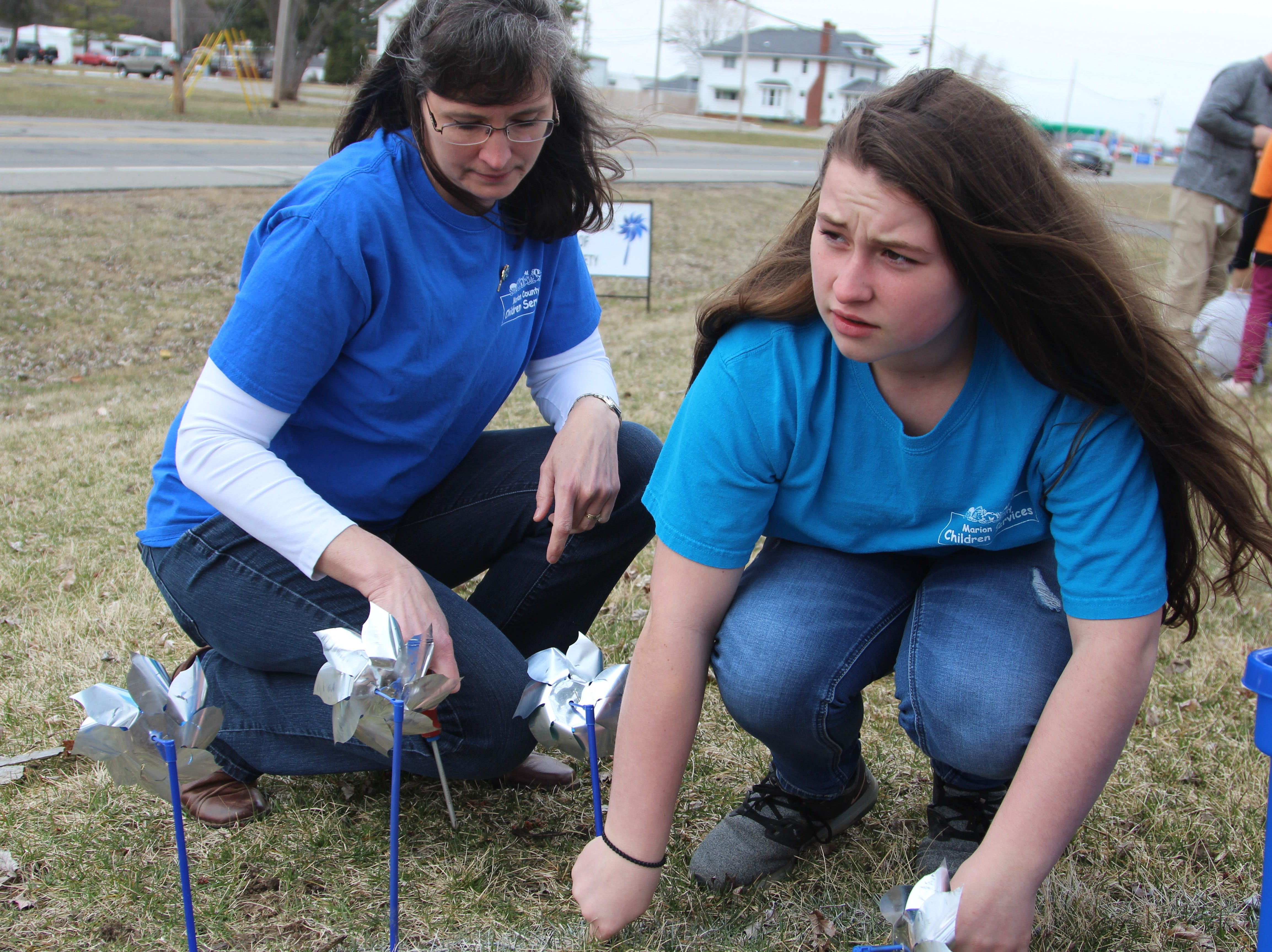 Hollianne Windle joins her mother Angela in planting pinwheels outside of Marion County Children Services on Thursday. Each one represents a safety assessment completed by the agency last year.