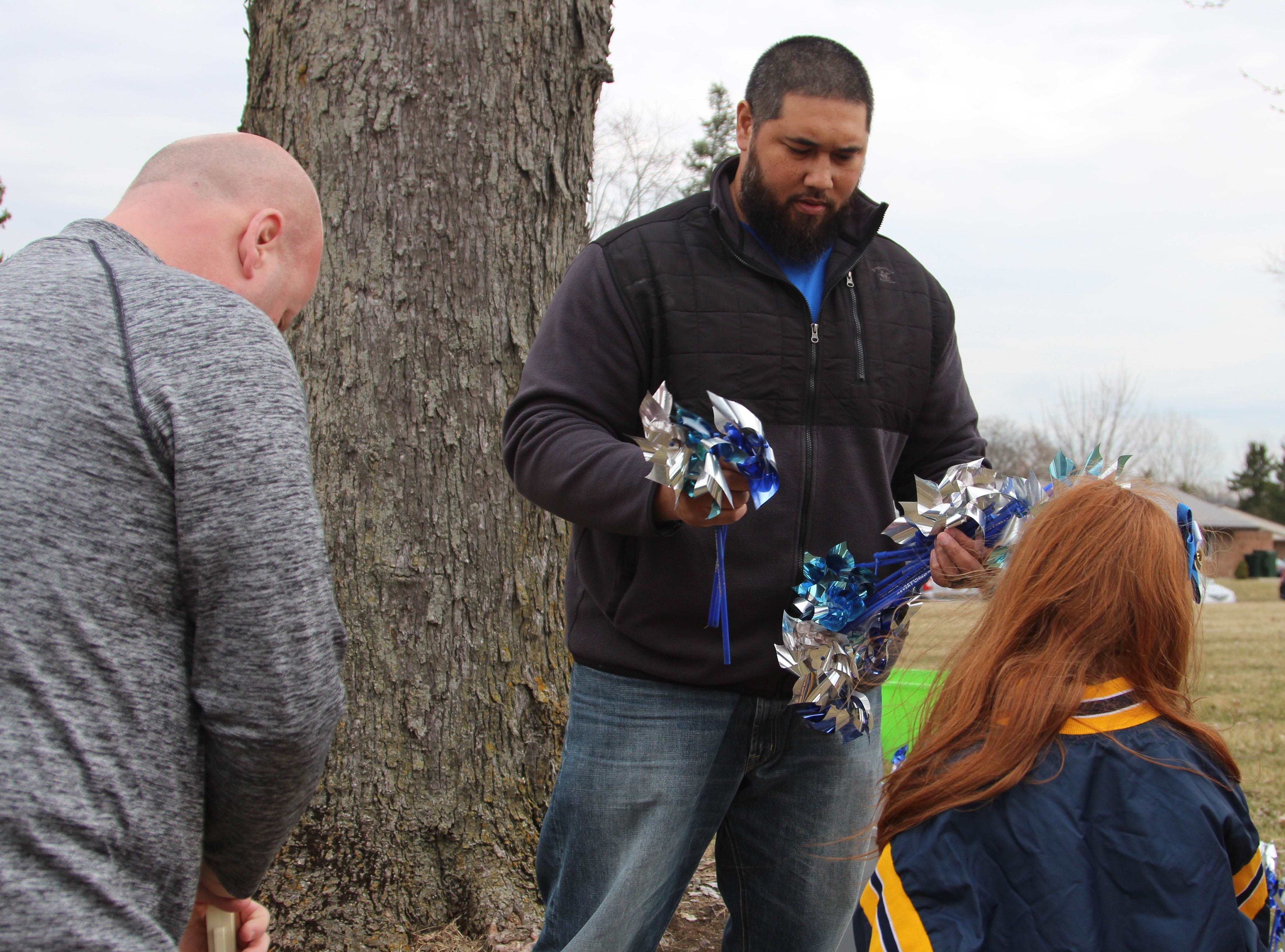 "Stephen Sene with Marion County Children Services passes out pinwheels on Thursday as part of the nationwide public awareness campaign ""Pinwheels for Prevention."""