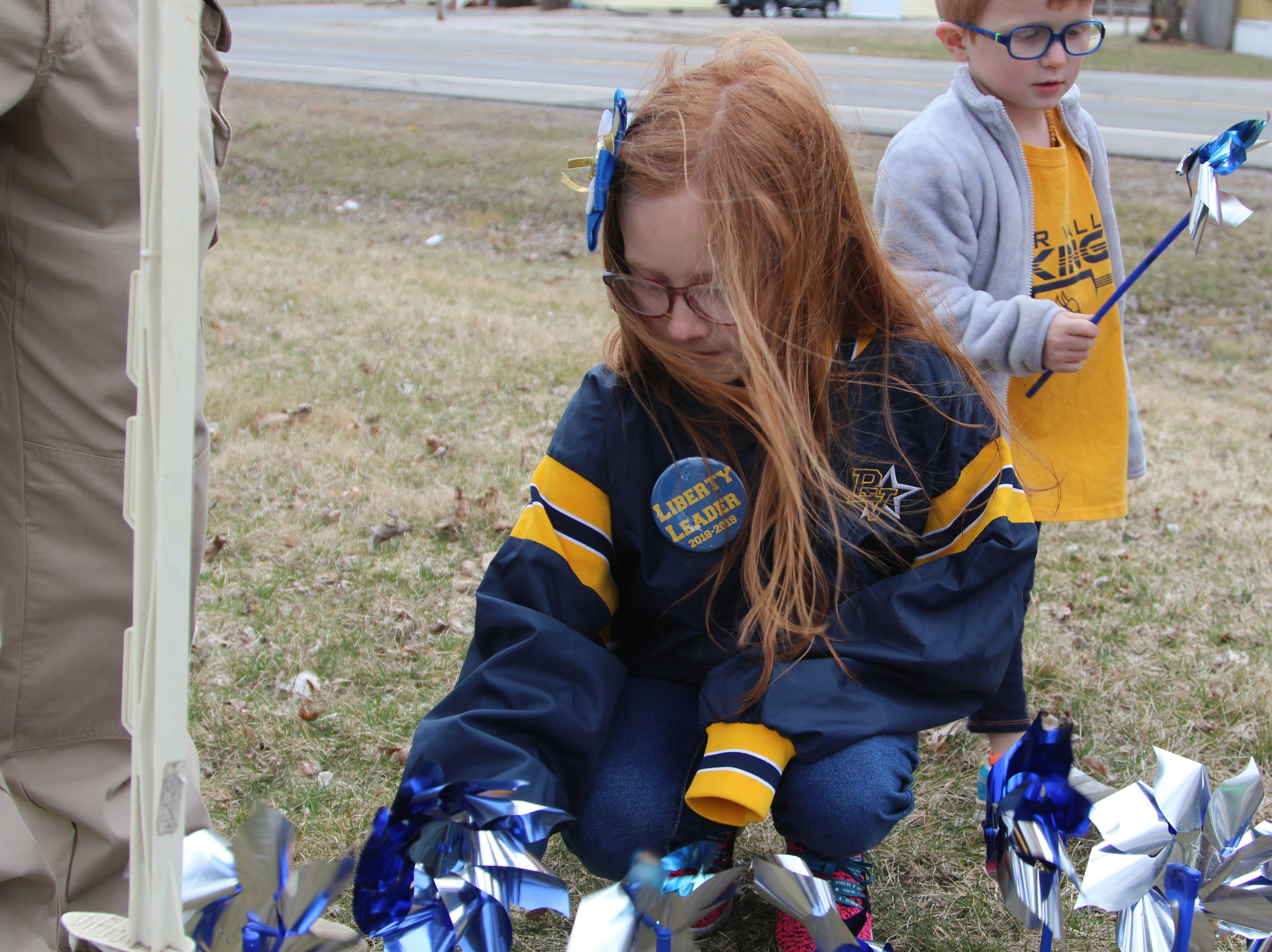 Scarlett Roston plants a pinwheel alongside her younger brother Reid on Thursday. They were part of a handful  of Liberty Elementary students that took part in the annual tradition outside Marion County Children Services.