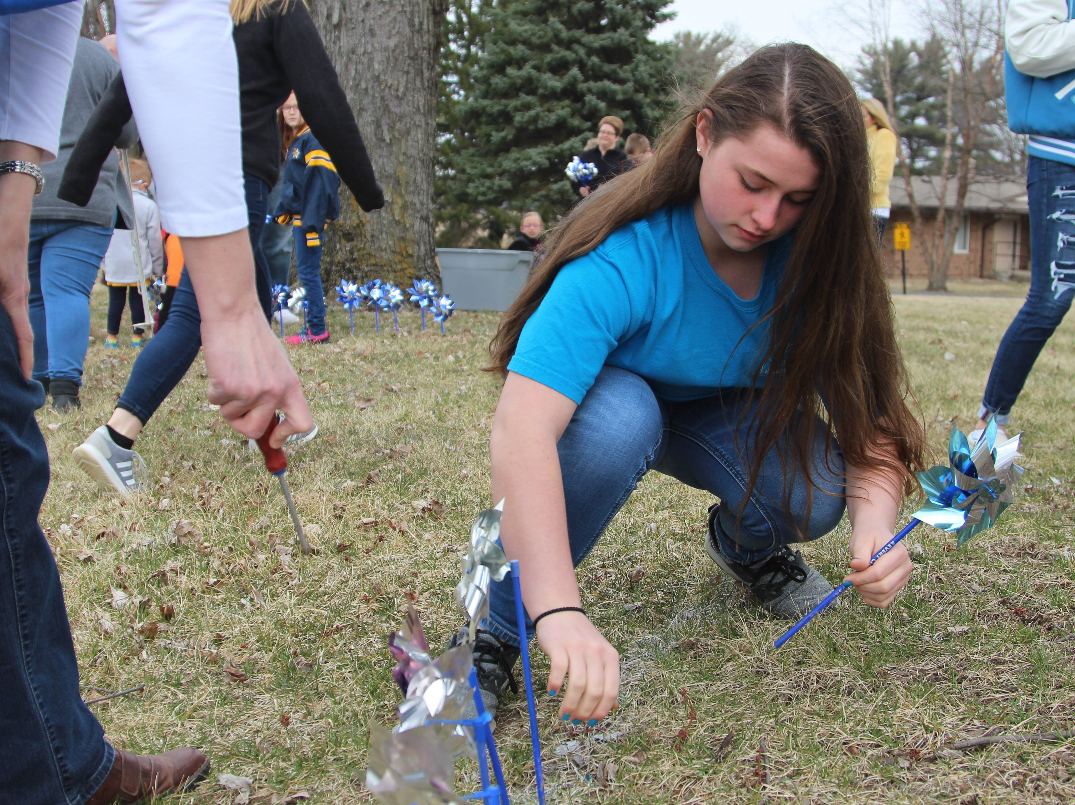 Hollianne Windle plants several pinwheels on Thursday representing a case of child abuse or neglect in the county in 2018. Marion County Children Services handled 931 safety assessments that year.