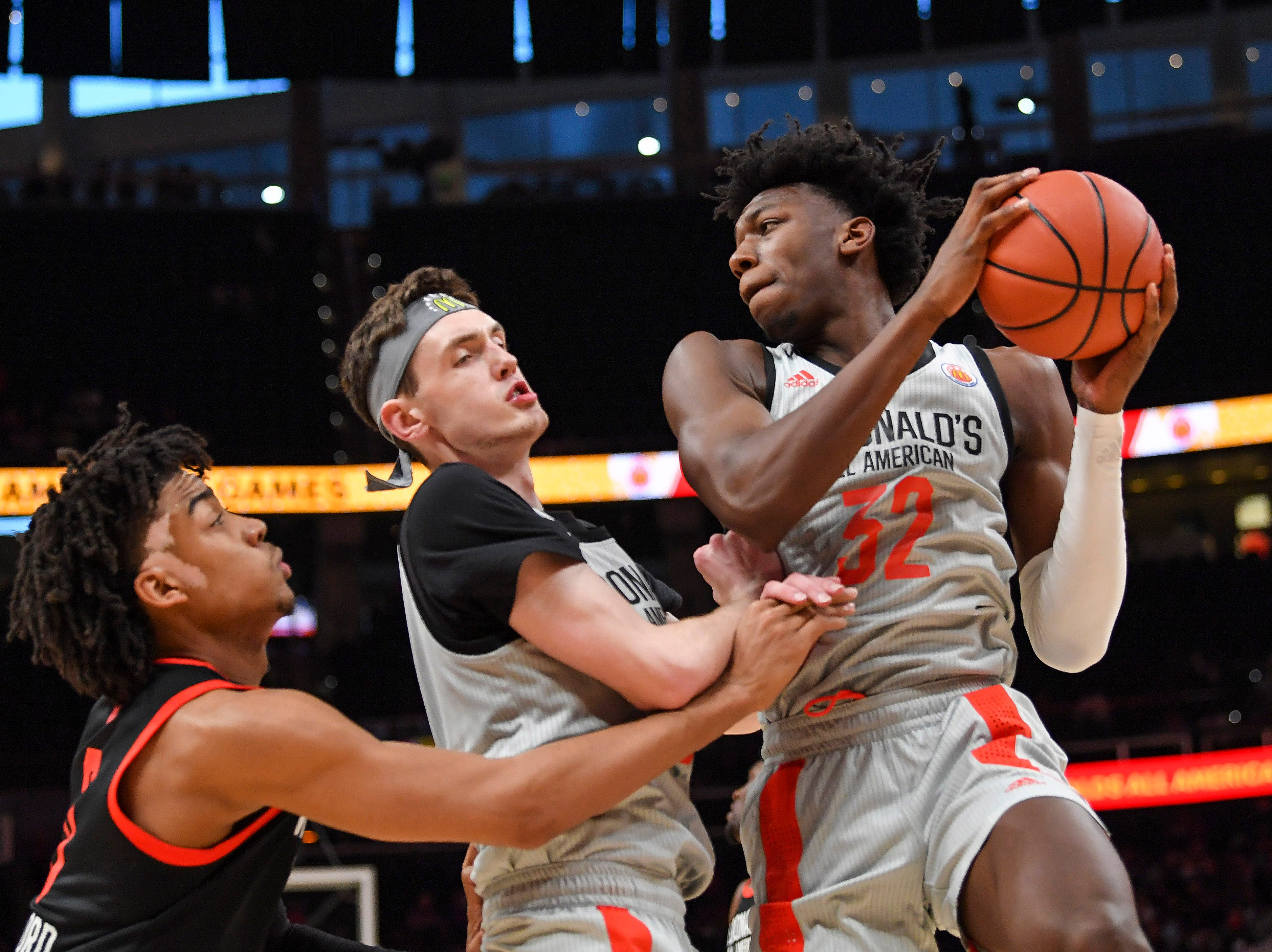 West Team's James Wiseman (32) grabs a rebound with Matthew Hurt (middle) and the East's Trenton Watford at the McDonald's All-American Game on   March 27, 2019, in Atlanta.